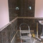 Back in the wetroom tiling the walls, again with tiles matching the originals